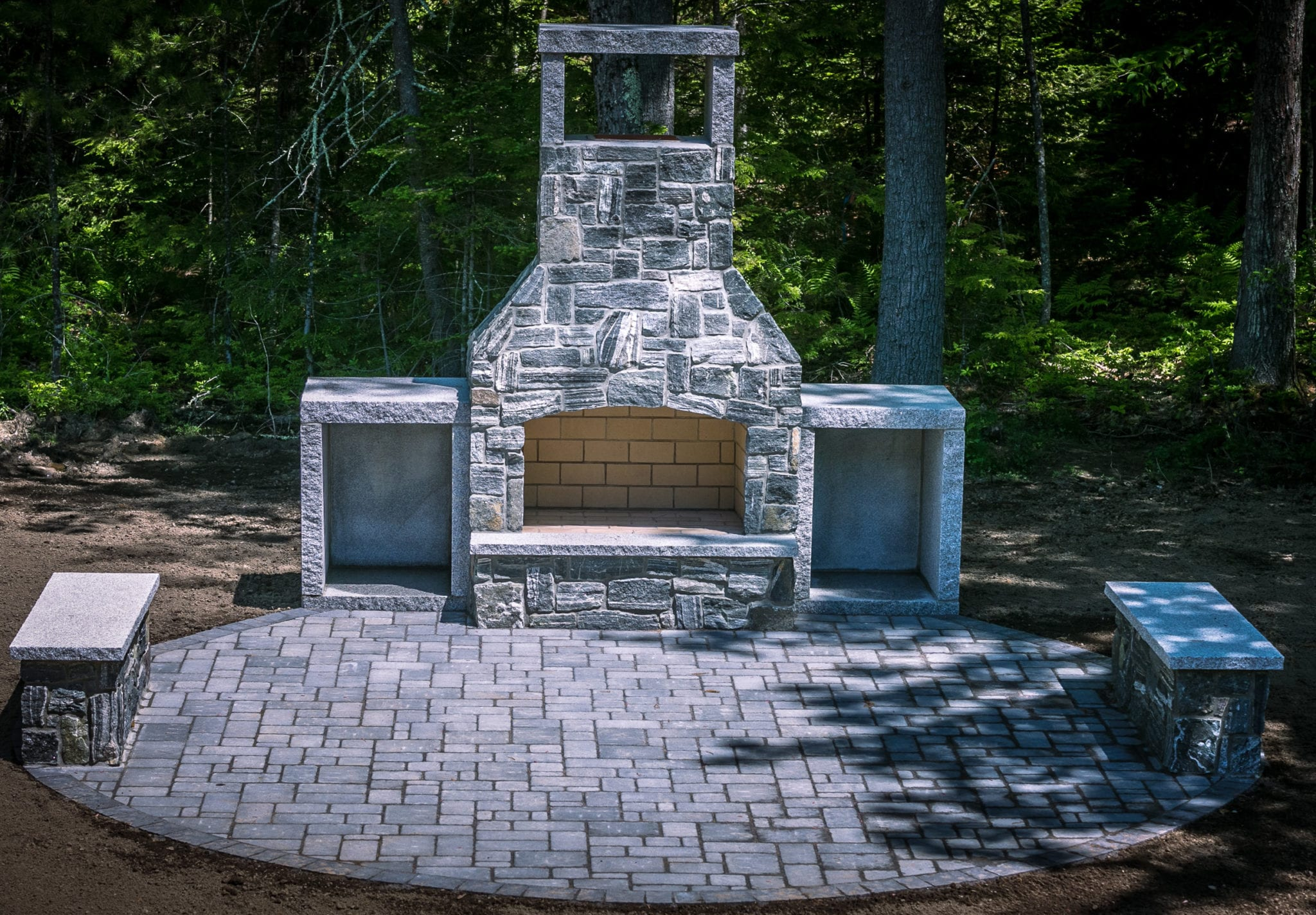 Outdoor Stone Fireplace with granite patio and firewood boxes
