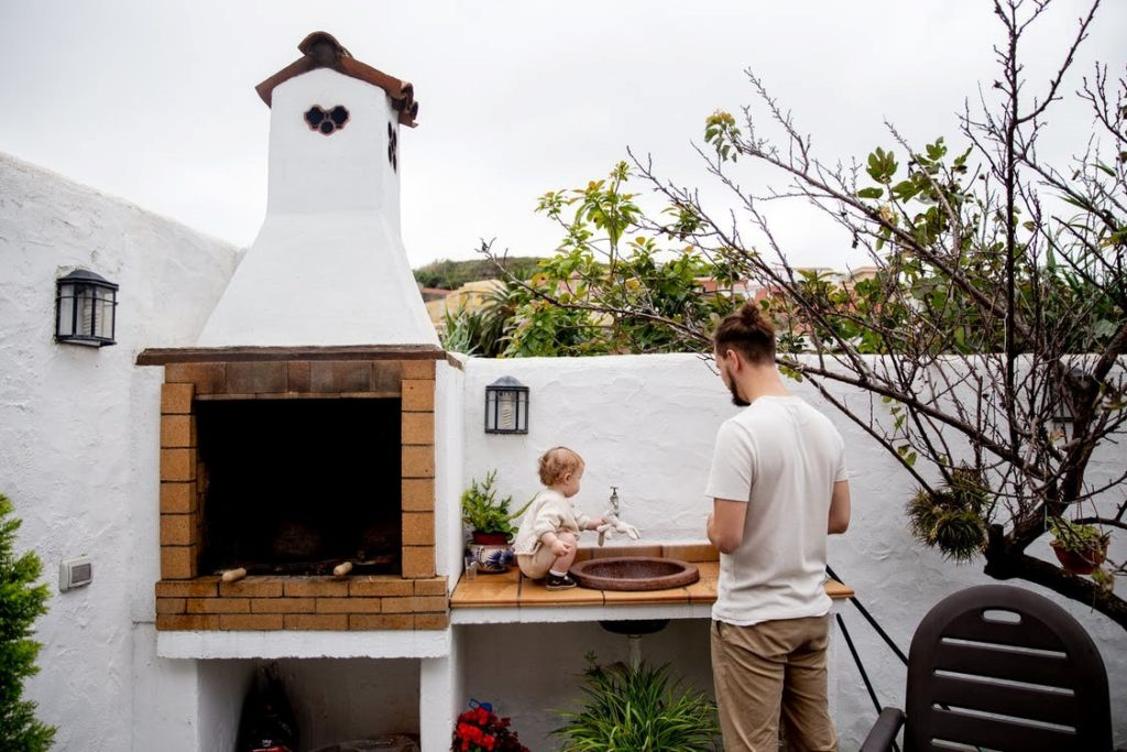 A man and a child standing near an out door brick piza oven