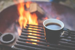 A cup of coffee with a fire pit in the background.