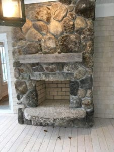 A living room with a magnificent stone wall fireplace.