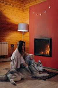 A women snuggling with her dog on a hearth rug in front of their fireplace.